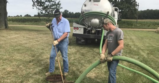 Two men pumping a septic tank