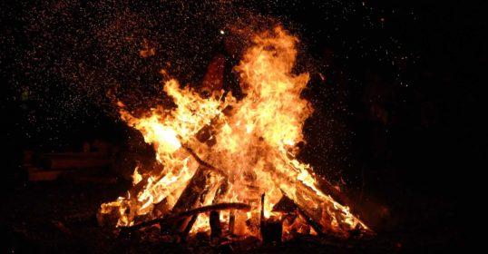 Bonfire burning under a dark sky